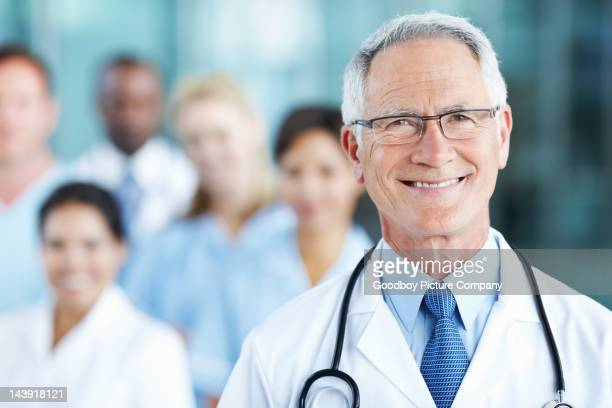 Smiling, male doctor with confident team