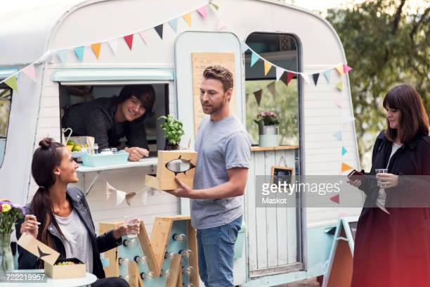 Smiling male owner looking at customers talking outside food truck