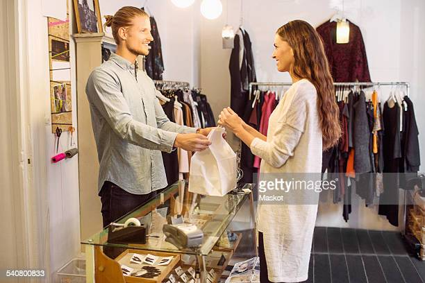 Smiling male sales person handing over shopping bag to female customer in boutique