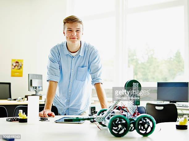 Smiling male student in classroom with robot