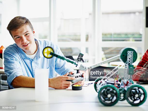 Smiling male student operating robot in classroom
