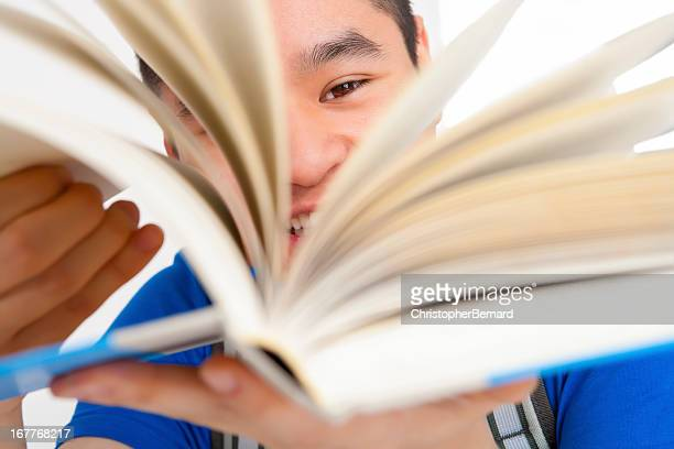Smiling male student turning pages