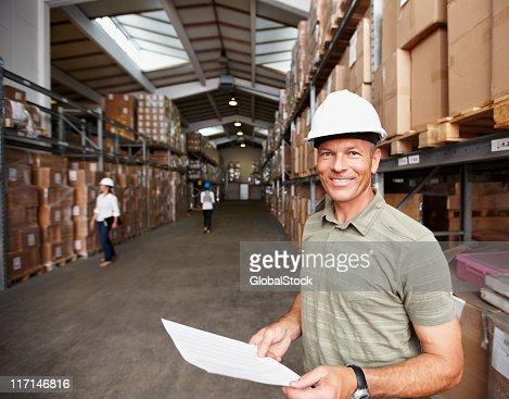 Lächelnd männlichen leitender Mitarbeiter bei Arbeitnehmer im warehouse : Stock-Foto