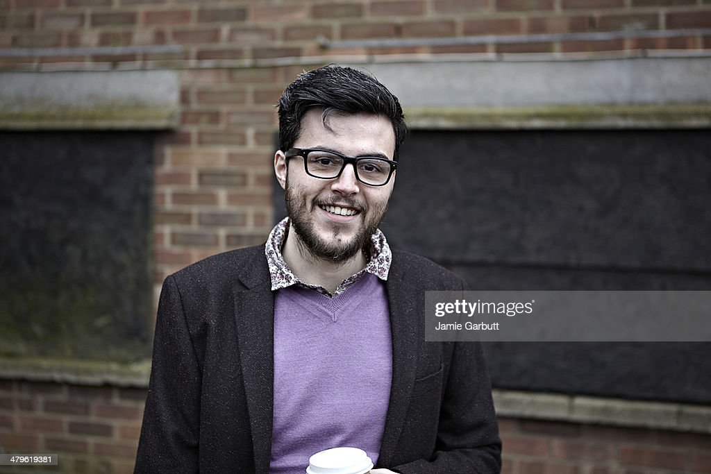 Smiling male with glasses holding a coffee