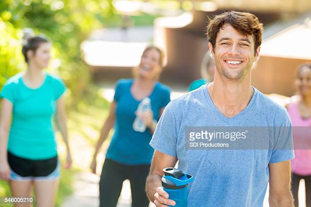 Smiling man and joyful people working out at a park