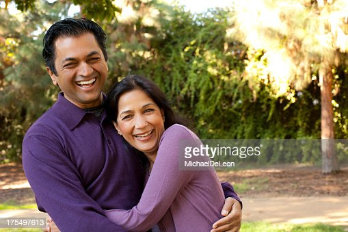 Smiling man and woman, both wearing purple, hugging outside