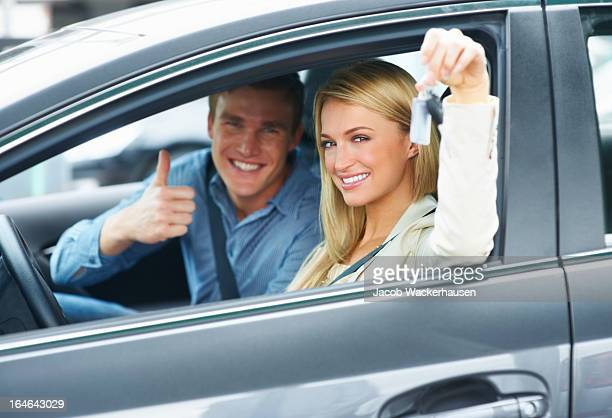Smiling man and woman in a new car