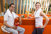 Young man and woman with towels around necks, drinking smoothies in bright sport bar after training and smiling at camera. Healthy lifestyle concept