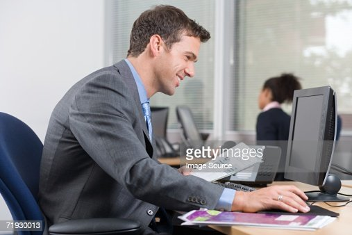 Smiling man at desk with a brochure : Bildbanksbilder