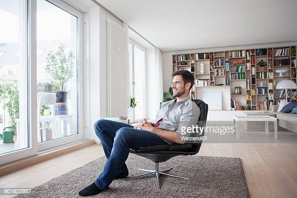 Smiling man at home sitting in armchair looking out of window