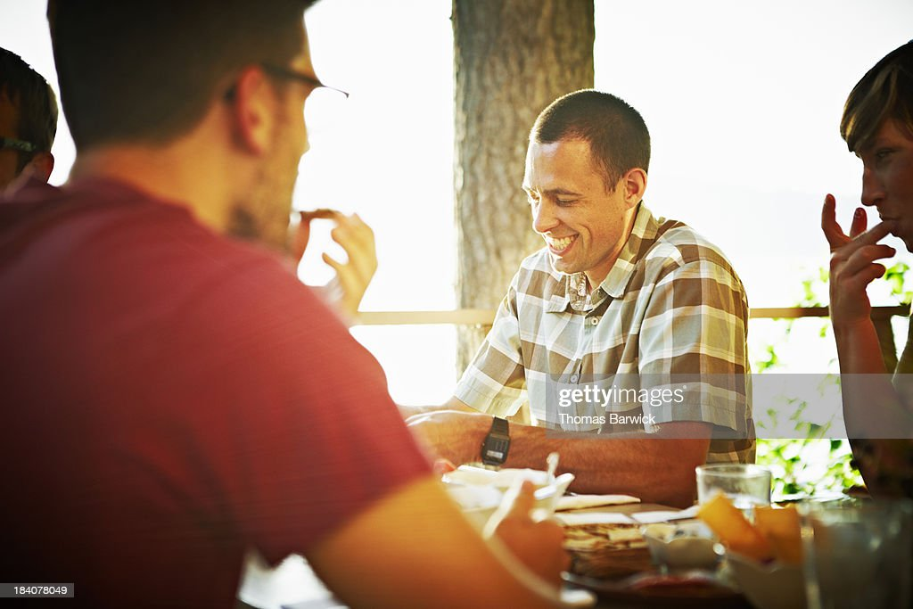 Smiling man at table sharing a meal with friends : Stock Photo