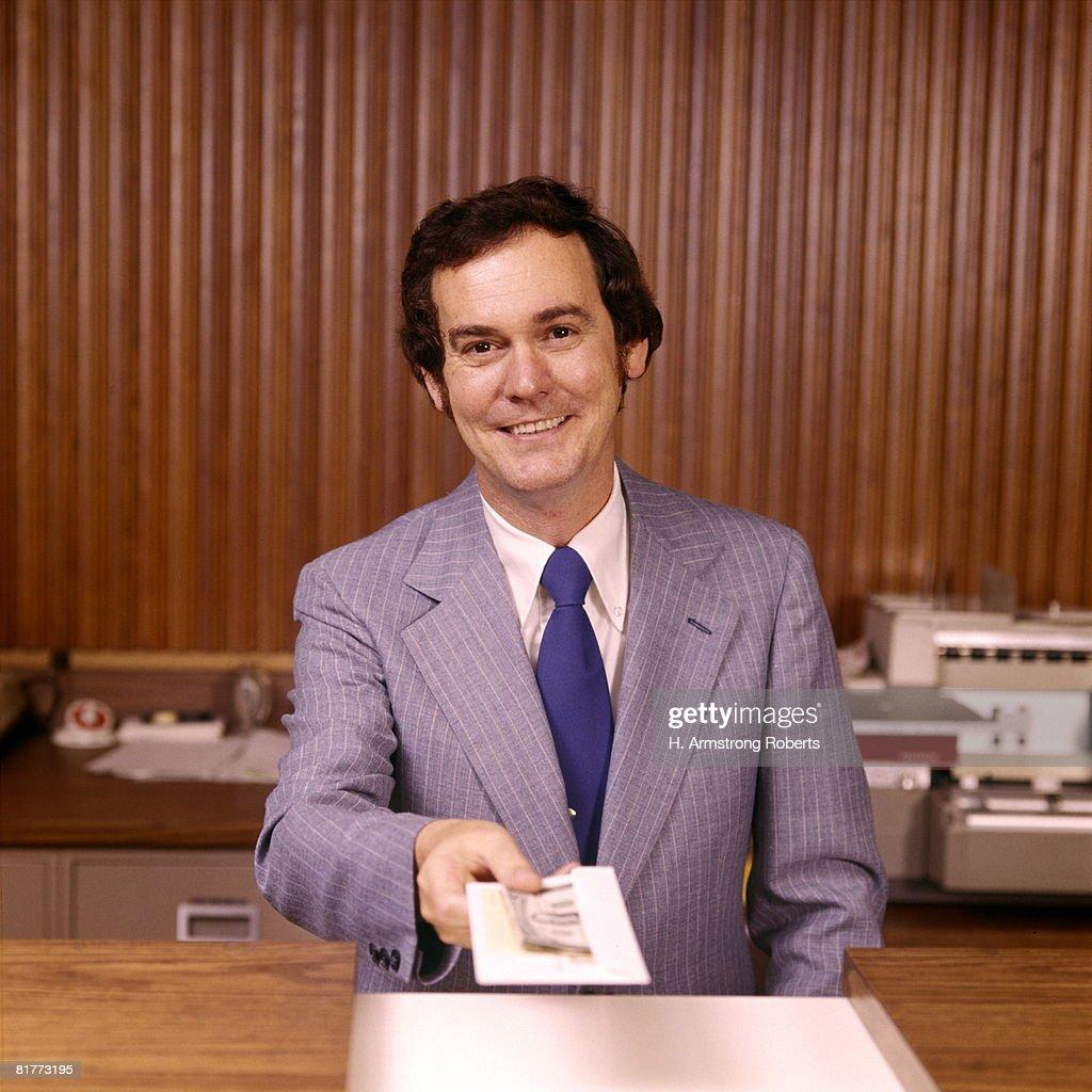 smiling man bank teller handing money receipt over counter banks tellers financial customer. Black Bedroom Furniture Sets. Home Design Ideas