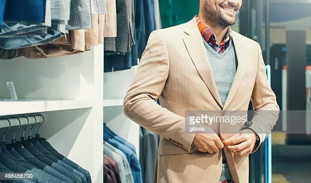 Uomo sorridente acquisto di alcuni capi in grandi magazzini.