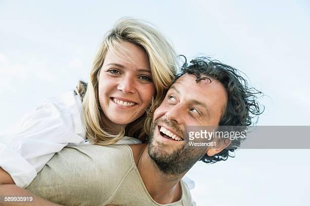 Smiling man carrying woman piggyback