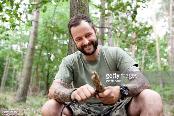 Smiling man carving in the forest