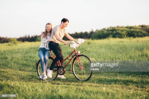 Lächelnder Mann Radfahren mit Frau zu Fuß auf der Wiese beim Sonnenuntergang