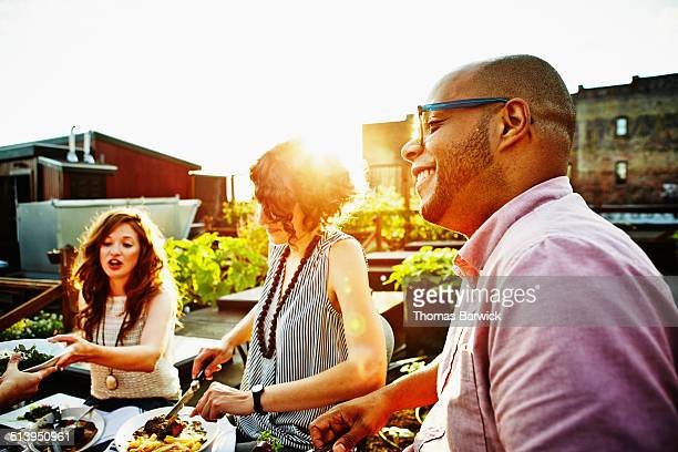 Smiling man dining with friends in rooftop garden
