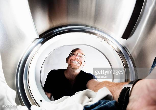 Smiling man doing laundry, seen from inside tumble dryer drum