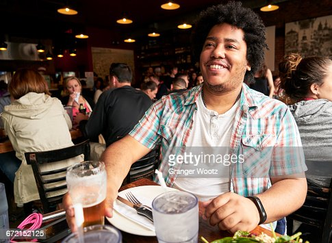 Smiling man drinking beer in restaurant
