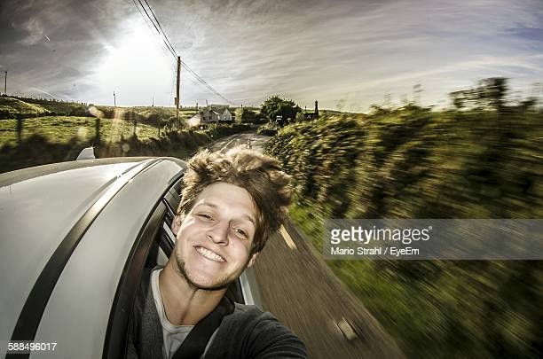 Smiling Man Driving Car Against Sky