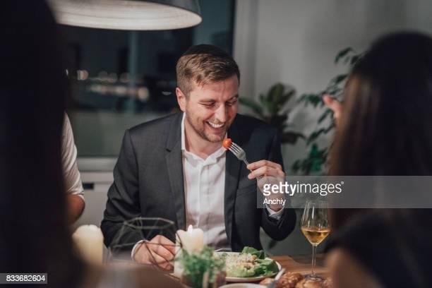 Smiling man eating a cherry tomato