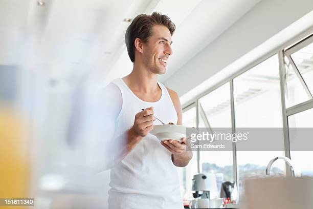 Smiling man eating cereal in kitchen