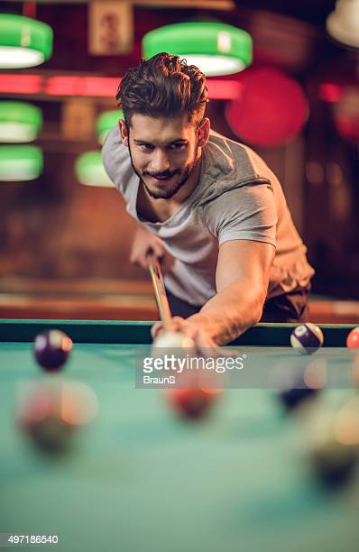Smiling man enjoying in a pool game at pub.