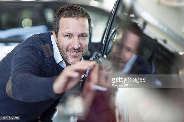 Smiling man examining new car at car dealership