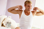 Smiling man getting out of bed