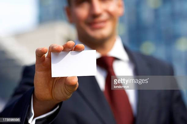 Smiling man giving his business card.