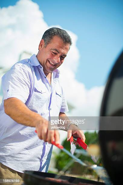 Smiling man grilling outdoors