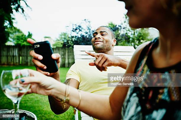 Smiling man hanging out with friends in backyard