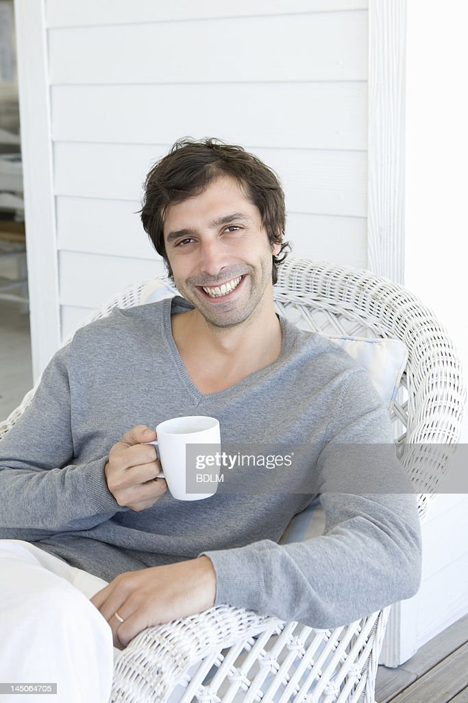 Smiling man having cup of coffee : Stock Photo