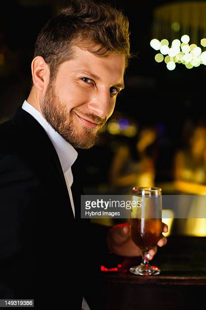 Smiling man having drink at bar