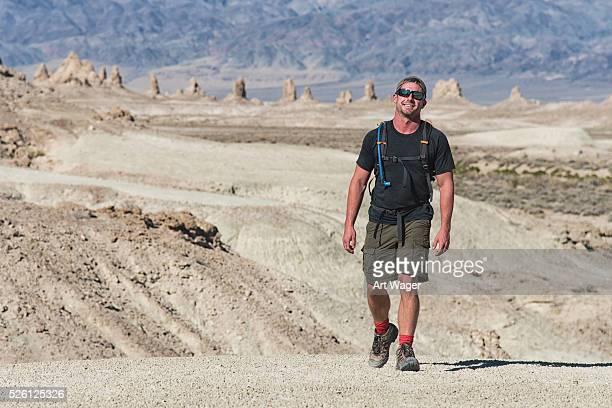 Smiling Man Hiking Across the Desert