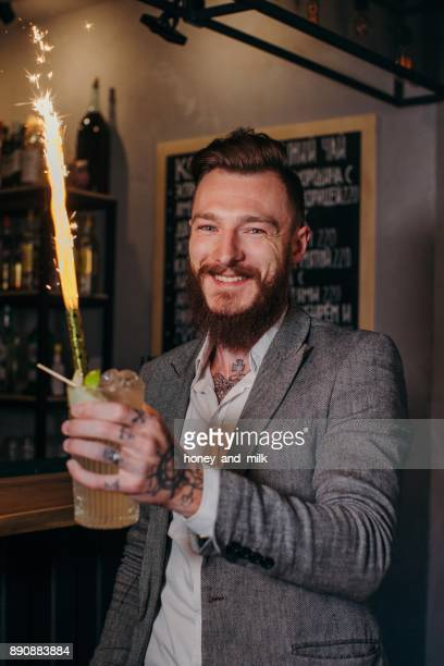 Smiling man holding a cocktail with a sparkler