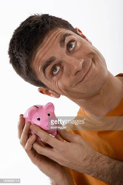 Smiling man holding a piggybank up to his ear