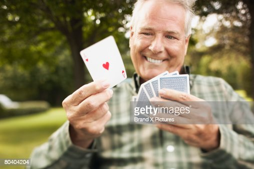 Smiling man holding ace of hearts : Foto stock
