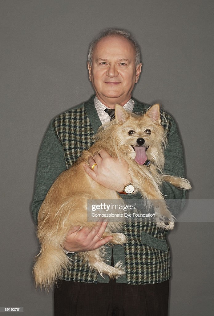 smiling man holding dog in his arms : Stock Photo