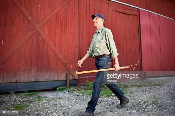 Smiling man holding gardening equipment while walking