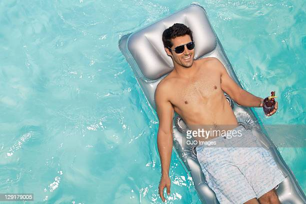 Smiling man holding glass while lying on raft