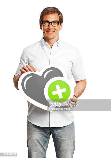 Smiling man holding heart sign isolated on white background.