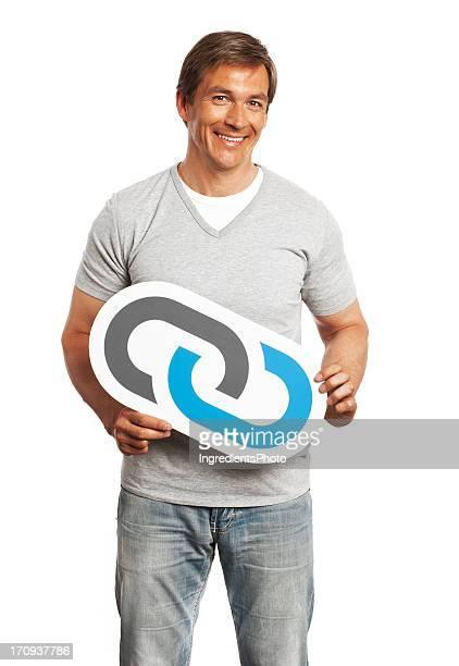 Lächelnder Mann hält link-Schild, isoliert auf weißem Hintergrund.
