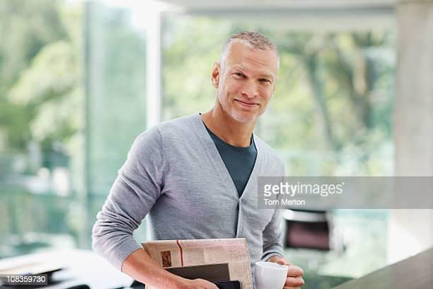 Homme souriant tenant un journal et une tasse à café