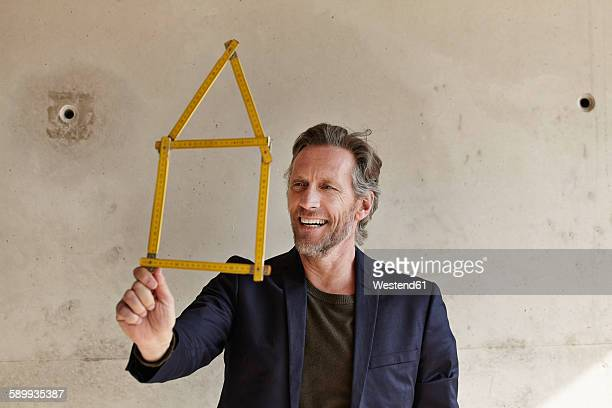 Smiling man holding pocket rule in shape of a house