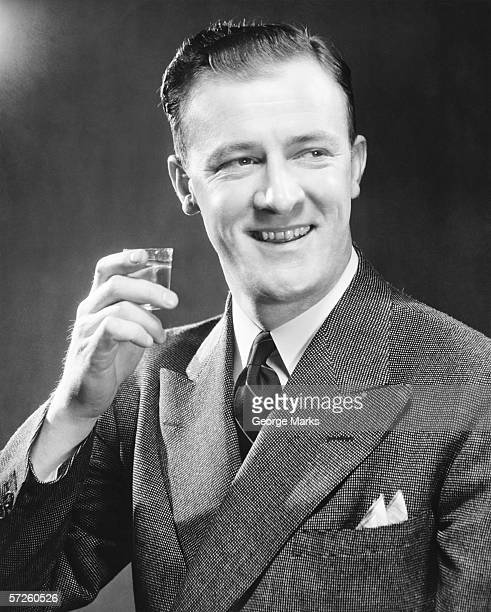 Smiling man holding up short glass with drink, (B&W), close-up