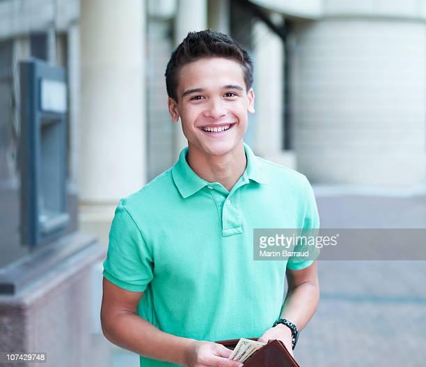 Smiling man holding wallet near ATM machine