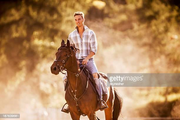 Smiling man horseback riding.