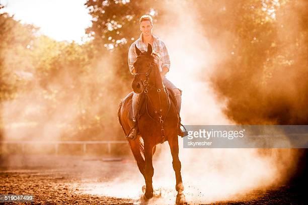 Homme souriant de l'équitation.