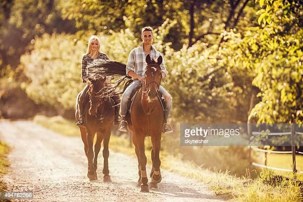Lächelnder Mann Reiten mit seiner Freundin in der Natur.